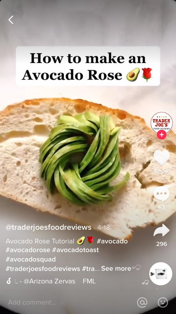 An avocado, shaped like a rose, sits on some toast.