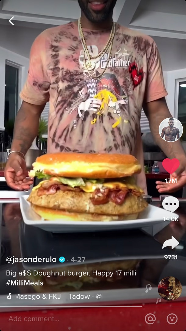 Jason Derulo goes to grab a giant donut burger that is sitting on a plate.