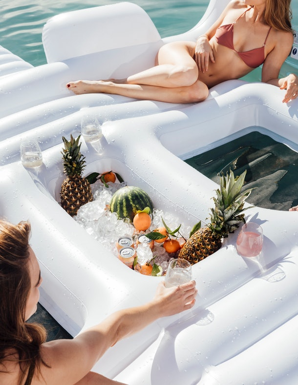 Two girls lounge on FUNBOY's Giant Dayclub pool float that has a cooler filled with drinks and fresh fruit.