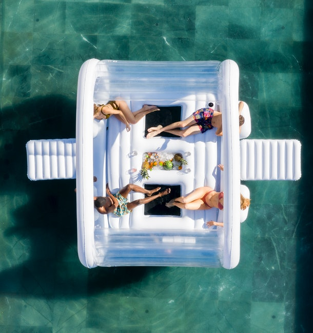 An aerial shot of a group of friends shows them hanging out in a pool on FUNBOY's Giant Dayclub pool float.