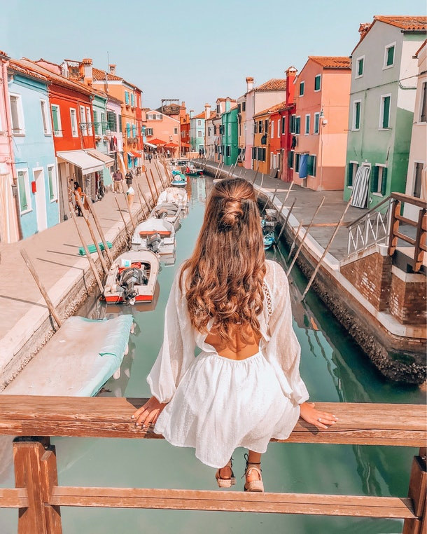 A brunette woman in a white sundress sits on a bridge overlooking a canal and colorful buildings in Italy.