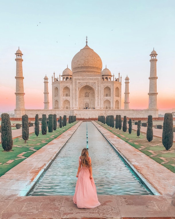A woman in a pink maxi gown stands in front of a small pool in front of the Taj Mahal at sunset.