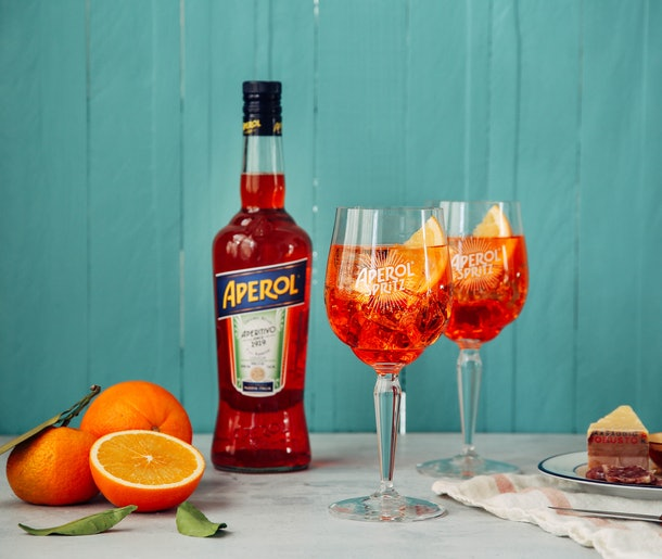 The ingredients for an Aperol Spritz sit on a table with a teal wall in the background.