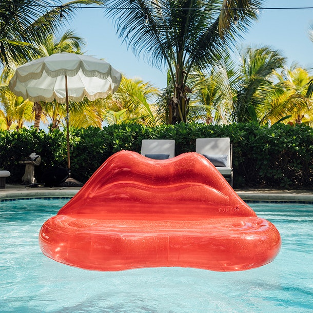 A clear red lips couch inflatable sits in a pool on a summer day.