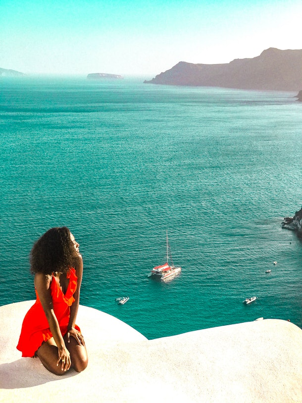 A woman in a bright red dress sits on a white stoop looking at the turquoise ocean water below.