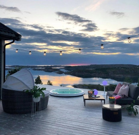 A patio overlooking a body of water has a circular hot tub and plush chairs.