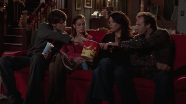 Dean hands Luke a bucket of popcorn at the movies in 'Gilmore Girls.'