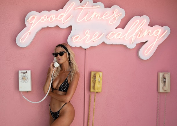 The Salty Blonde poses next to a pink wall and talks on a pay phone while wearing a black and white polka dot bathing suit.