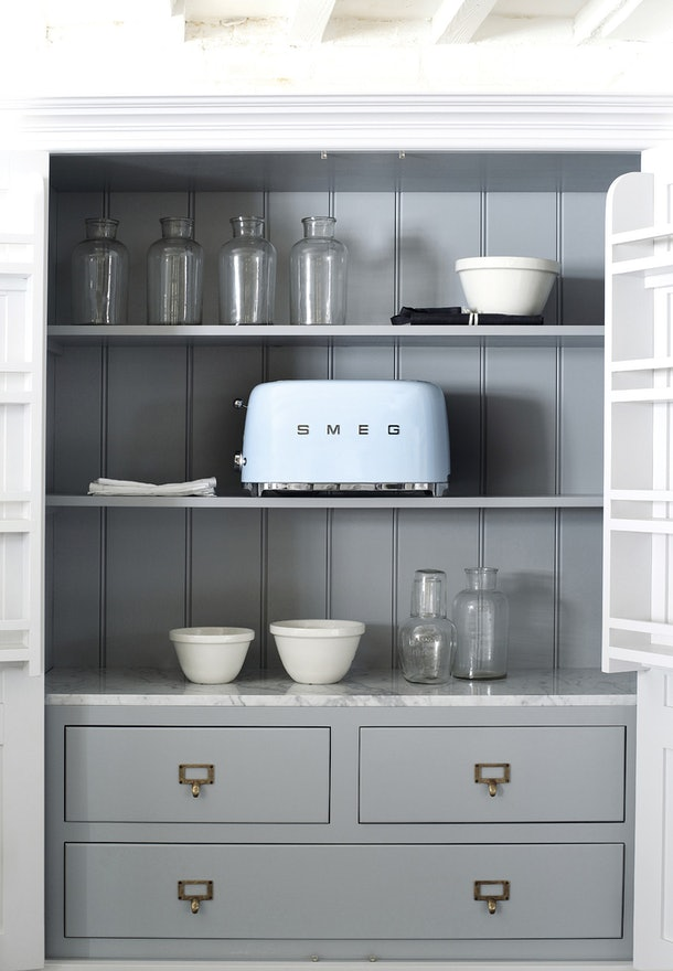 A light blue SMEG toaster sits in a cabinet with minimalistic vases and plates.