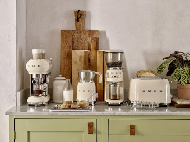 A set of cream SMEG appliances sit on a counter with breakfast food and ingredients.
