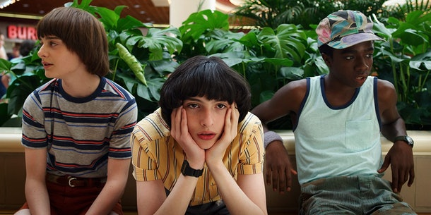 Will, Mike, and Lucas from Netflix's 'Stranger Things' sit on a bench at the Starcourt Mall and wait.