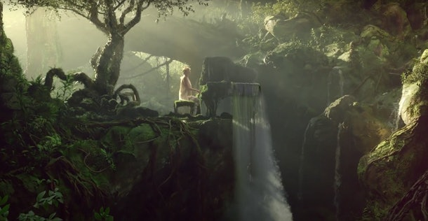 """Taylor Swift sits at a moss-covered piano in a lush jungle with a waterfall in her """"cardigan"""" music video."""