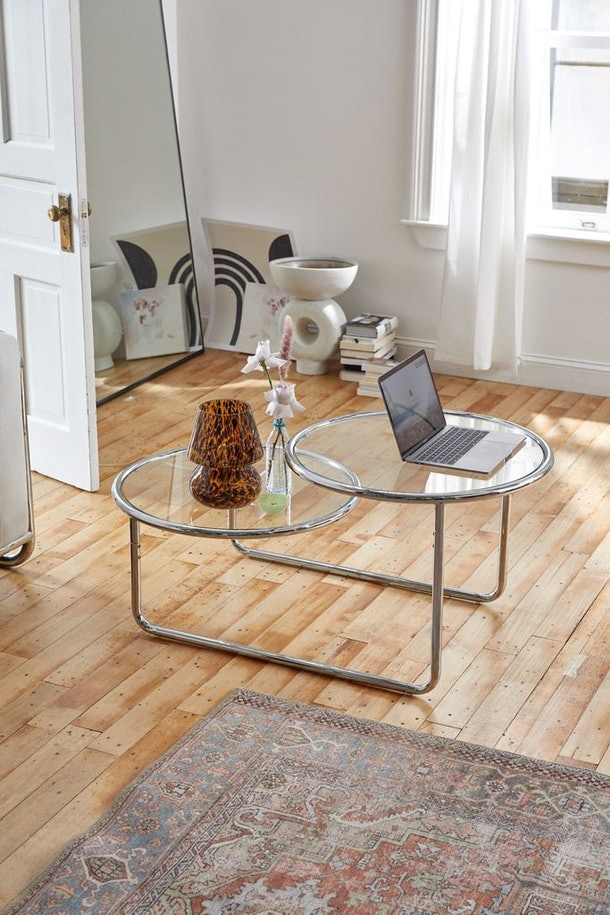 The Selene 2-Tier Coffee Table from Urban Outfitters sits in a modern-themed apartment with wood floors and funky art.