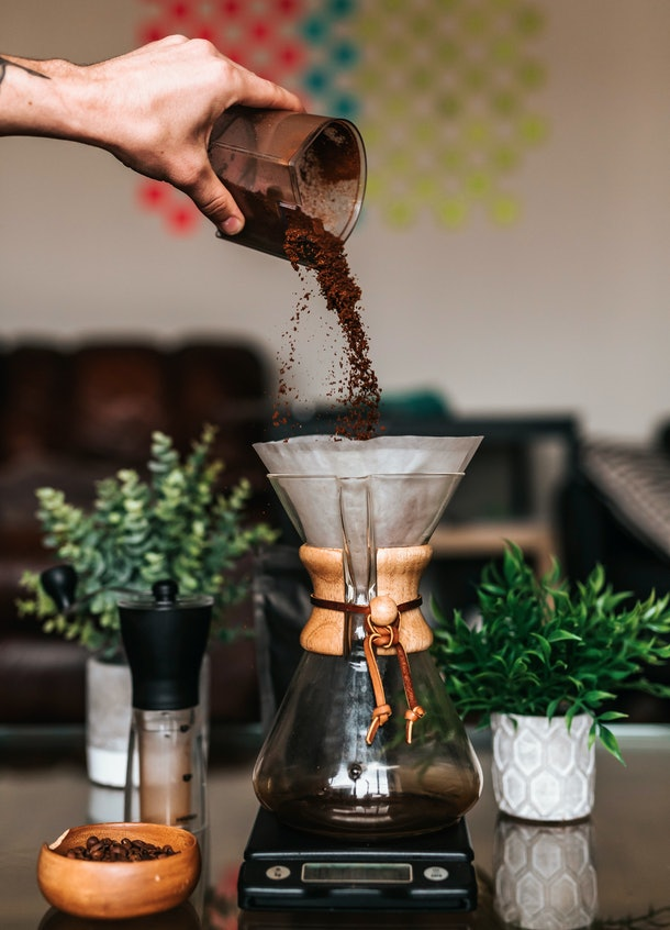 A young man pours coffee grounds into a pour over coffee machine surrounded by plants and coffee beans.