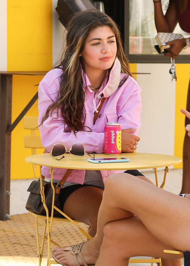 Hannah Ann Sluss from 'The Bachelor' sits at a yellow patio table and drinks a prebiotic soda from Poppi.
