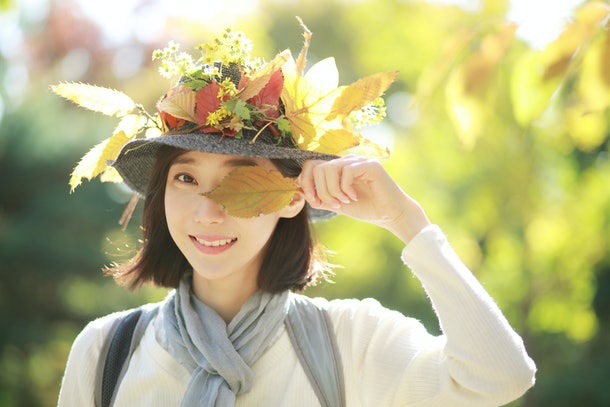 Young woman holding fall leaf