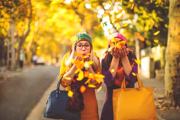 Young women blowing fall leaves
