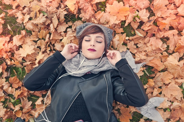 Young woman listening to music in fall