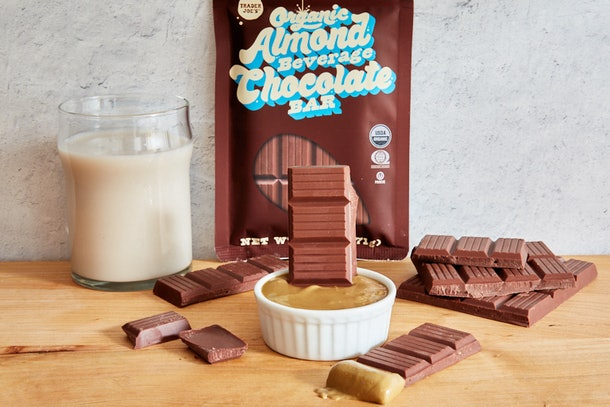 The Organic Almond Beverage Chocolate Bar from Trader Joe's sits on a wood table with almond milk and nut butter.