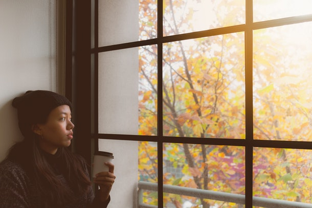 Young woman drinking coffee in autumn