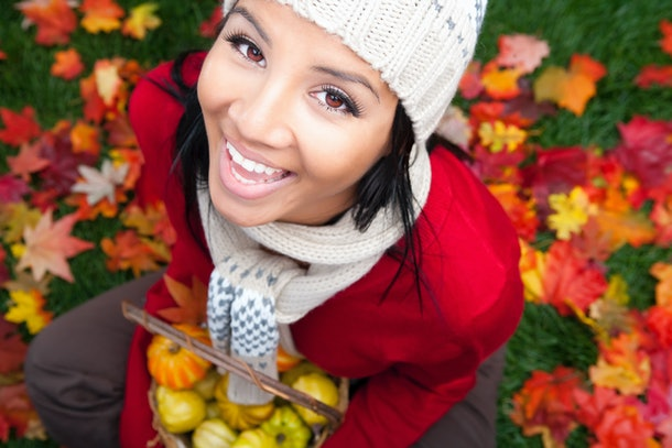 Young woman holding pumpkins in fall leaves