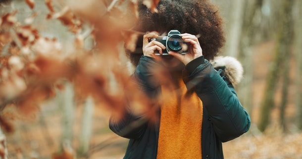 Young woman taking pictures of fall foliage