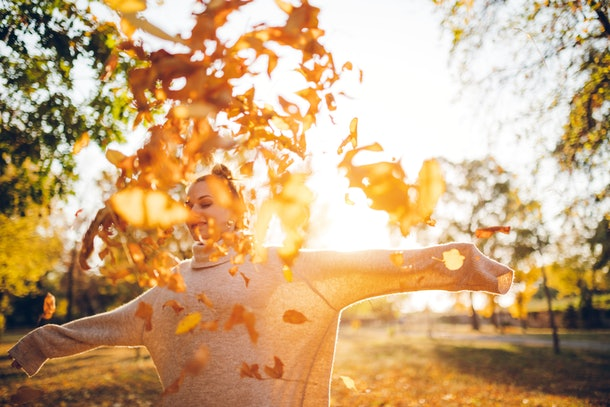 Young woman playing in fall leaves