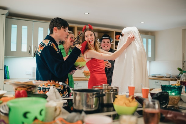 Friends laughing, eating on Halloween