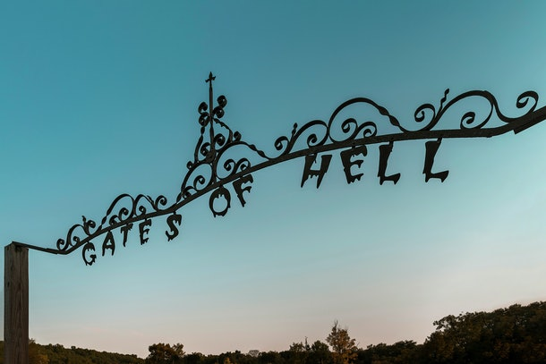 """The entrance to the """"Mayor of Hell"""" listing on Airbnb reads, """"Gates of Hell"""" as the sun sets."""
