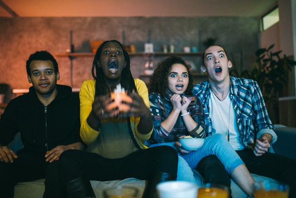 Young scared friends watching horror movie on TV at home