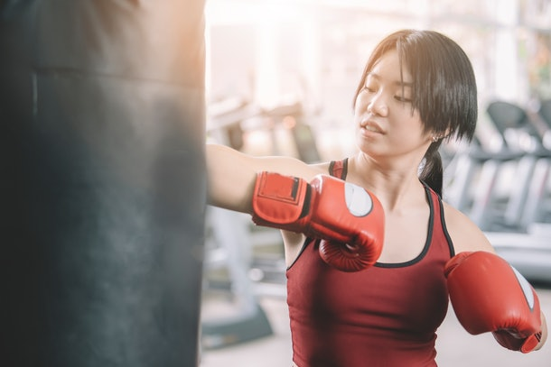 Young female athlete wearing boxing gloves workout