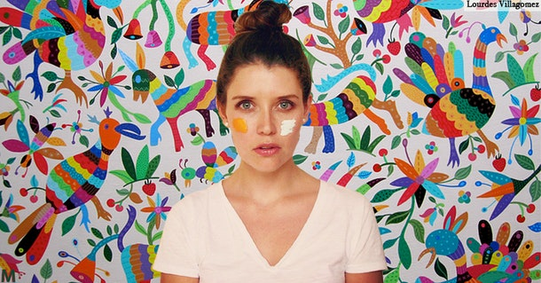 Lourdes Villagomez faces the camera with a dollop of orange paint on her left cheek and a dollop of white paint on her right cheek. The backdrop is colorful stylized birds on a white background.