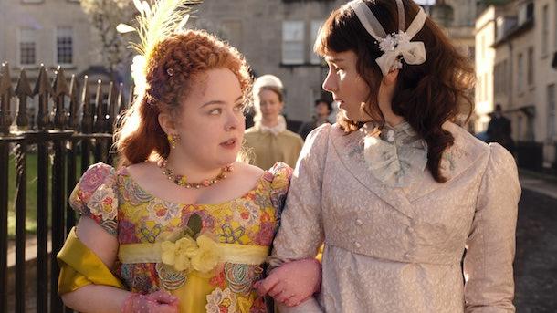 Penelope Featherington and Eloise Bridgerton go for a walk together outside in 'Bridgerton.'