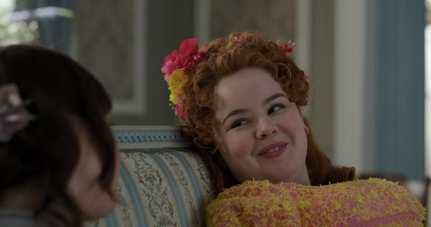 """Penelope from """"Bridgerton"""" smiles at Eloise on the couch."""