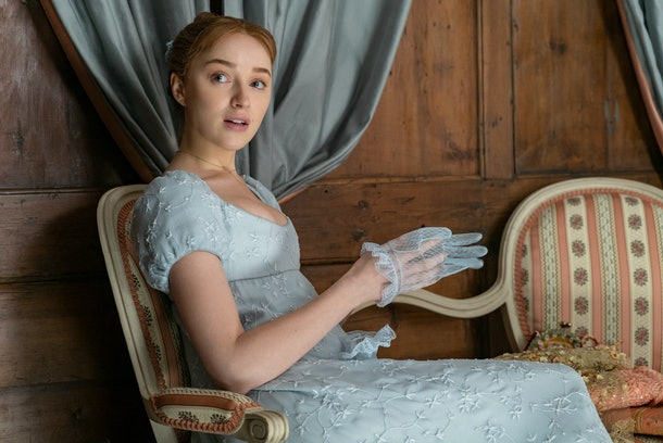 Daphne Bridgerton sits in a chair while pulling off her gloves in 'Bridgerton.'