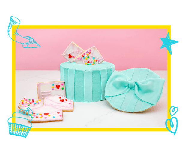 A teal hat box cake with love letter cookies based on 'To All the Boys I've Loved Before' is placed on a counter.