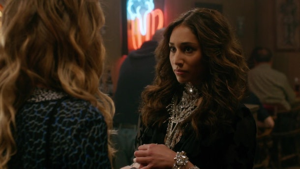 Klair talks to Alexis Rose at a bar while looking totally glam in a large statement necklace in 'Schitt's Creek.'