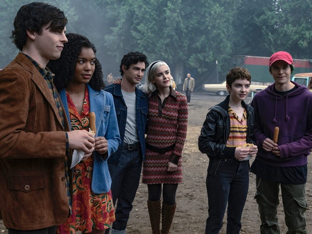 Sabrina and her friends from 'Chilling Adventures of Sabrina' stand around together in couple pairs outside.