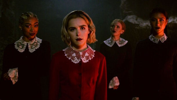 Sabrina and the Weird Sisters stand together in similar dresses in 'Chilling Adventures of Sabrina.'