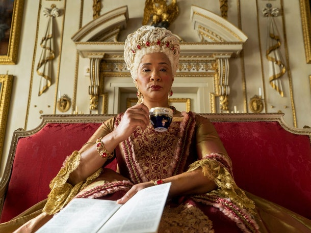 The Queen in 'Bridgerton' sips her tea while holding Lady Whistledown's paper.