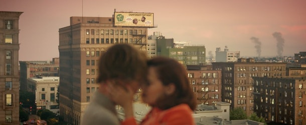 """A young couple kiss on a rooftop in the city at sunset during Justin Bieber's """"Anyone"""" music video."""