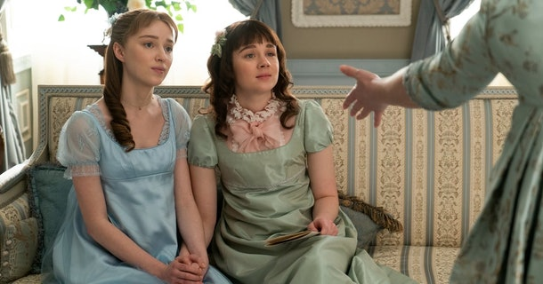 Daphne and Eloise from 'Bridgerton' hold hands in silk dresses while sitting on a couch.