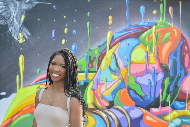 Aalayah Eastmond, wearing a beige tank top and gold necklace, smiles in three-quarter profile standing in front of a multcolored abstract mural