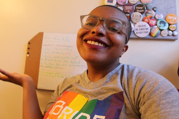 A selfie of Ose Arhegan, wearing a colorful Pride shirt, smiling into a camera in front of a whiteboard and array of activism pins and buttons