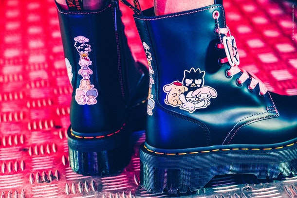 Dr. Martens x Hello Kitty Jadon boots being modeled in an arcade.