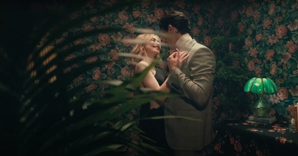 "Sabrina Carpenter dances with Gavin Leatherwood behind a leafy plant in the ""Skin"" music video."