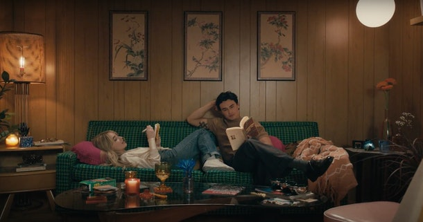 "Sabrina Carpenter journals on the couch while Gavin Leatherwood reads a book during the ""Skin"" music video."