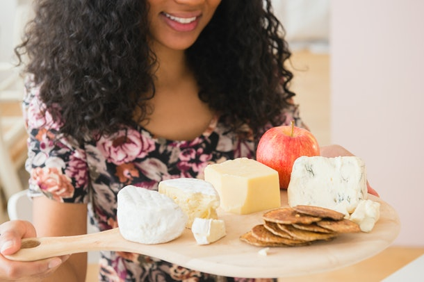 woman carrying fruit and cheese board