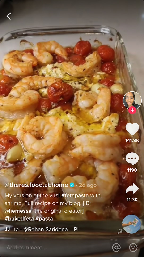 This feta pasta recipe includes cherry tomatoes, olive oil, and jumbo shrimp in a baking pan.