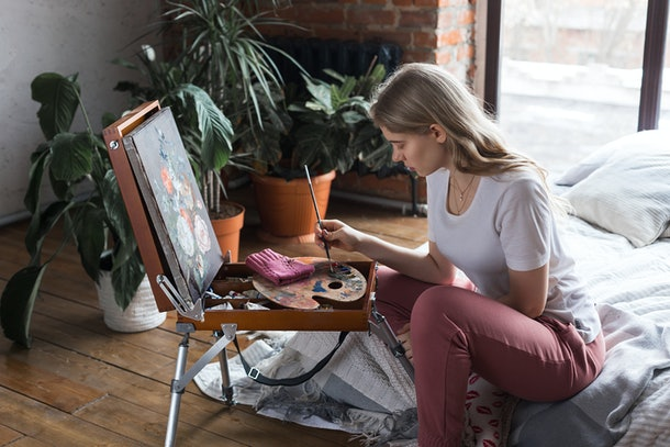 Young pretty blonde girl with brush and palette sitting near easel drawing picture in a studio. Art, creativity, hobby concept, painting process.